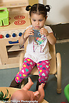 Education Preschool Child care two year old program   toddler girl using camerasto take photo of baby doll