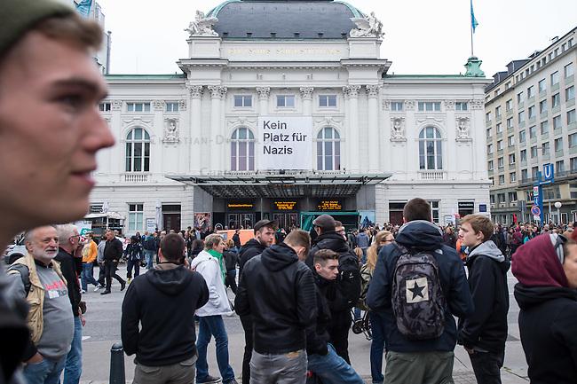 """Proteste gegen Naziaufmarsch """"Tag der Patrioten"""".<br /> Mehere zehntausend Menschen protestirten am Samstag den 12. September 2015 in Hamburg gegen einen von Nazis und Hooligans geplanten Aufmarsch unter dem Motto """"Tag der Patrioten"""". Der Aufmarsch war im Vorfeld gerichtlich untersagt worden, da davon auszugehen sei, dass von ihm Gewalttaten gegen Personen ausgehen wuerden. Die Nazis wichen am Samstag daraufhin nach Bremen aus, wo der Aufmarsch jedoch auch untersagt wurde.<br /> Trotz Verbot versammelten sich an verschiedenen Orten in Hamburg mehrere zehntausend Menschen und protestierten gegen Rassismus und fuer ein Bleiberecht fuer gefluechtete Menschen.<br /> Vor dem Hauptbahnhof kam es zu kleineren Auseinandersetzungen mit der Polizei, die mit 8 Wasserwerfern, Polizeihubschrauber und Beamten aus Bayern, Schleswig-Holstein, Baden-Wuertemberg und Hamburg im Einsatz war.<br /> Als eine Gruppe von ca. 10 bis 15 Nazis und Hooligans im Hauptbahnhof Menschen angriffen, drohte die Lage kurzzeitig zu eskalieren. Die Angreifer mussten aber vor Gegendemonstranten in einen Zug fluechten, wo sie von der Polizei festgesetzt wurden. Der Verkehr durch den Hauptbahnhof war ueber lange Zeit eingestellt, da die Polizei weitere Nazis und Hooligans in ankommenden Zuegen befuerchtete und Auseinandersetzungen verhindern wollte.<br /> Im Bild: Gegendemonstranten vor dem Hauptbahnhof. An der Fassade des Deutschen Theater wurde fuer den Tag ein Transparent """"Kein Platz fuer Nazis"""" aufgehaengt.<br /> 12.9.2015, Hamburg<br /> Copyright: Christian-Ditsch.de<br /> [Inhaltsveraendernde Manipulation des Fotos nur nach ausdruecklicher Genehmigung des Fotografen. Vereinbarungen ueber Abtretung von Persoenlichkeitsrechten/Model Release der abgebildeten Person/Personen liegen nicht vor. NO MODEL RELEASE! Nur fuer Redaktionelle Zwecke. Don't publish without copyright Christian-Ditsch.de, Veroeffentlichung nur mit Fotografennennung, sowie gegen Honorar, MwSt. und Beleg. Konto: I N G - D i B a, IBAN D"""