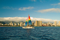 The billowing multi-colored sails of a catamaran gliding off the Honolulu coastline with the Koolau mountains capped with clouds in the background.