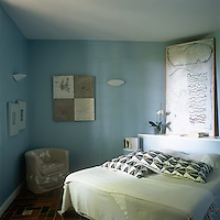 A blue bedroom with a tiled floor. A double bed is placed at an angle with a shelf as headboard in the corner.