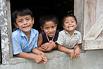 Portrait of Mayan boys in the window of a cinderblock home in the Mayan community of San Miguel, Toledo, Belize
