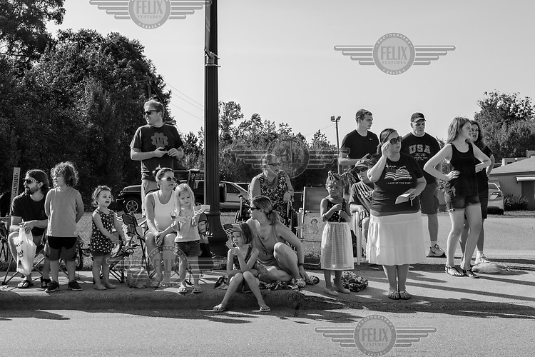 Spectators line the street at a July 4th Parade.