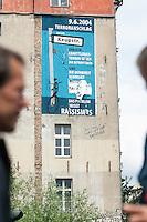 """Das Berliner Landeskriminalamt LKA veranlasste  am Vormittag des 3. Juni 2014 die Entfernung des Satzes """"NSU Staat und Nazis Hand in Hand"""". Der Staat werde damit laut. §90a verunglimpft. Wegen angeblicher """"Gefahr im Verzug"""" musste de Feuerwehr anruecken und den Satz aus dem Plakat schneiden. Von umstehenden Personen und Journalisten wurden die Personalien aufgenommen.<br /> Das Plakat war kurz zuvor an der Hauswand angebracht worden.<br /> 3.6.2014, Berlin<br /> Copyright: Christian-Ditsch.de<br /> [Inhaltsveraendernde Manipulation des Fotos nur nach ausdruecklicher Genehmigung des Fotografen. Vereinbarungen ueber Abtretung von Persoenlichkeitsrechten/Model Release der abgebildeten Person/Personen liegen nicht vor. NO MODEL RELEASE! Don't publish without copyright Christian-Ditsch.de, Veroeffentlichung nur mit Fotografennennung, sowie gegen Honorar, MwSt. und Beleg. Konto:, I N G - D i B a, IBAN DE58500105175400192269, BIC INGDDEFFXXX, Kontakt: post@christian-ditsch.de]"""