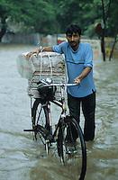 INDIA, Mumbai, Bombay, heavy monsoon rains flood the streets, transport of newspaper by Hero bicycle / INDIEN, Mumbai, schwere Monsun Regen ueberfluten die Strassen, Transport von Zeitungen per Fahrrad