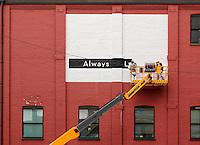 Men painting a sign on the facade of a building, Lancaster, Pennsylvania, USA