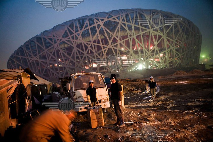 Migrant workers on the site of the Bird's Nest stadium built for the 2008 Olympic Games. They buy scrap metal from construction workers who collect these recyclable materials from previously demolished buildings at this site.