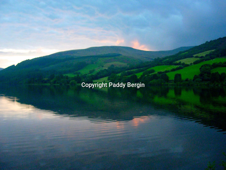 Landscape reflected in the reservoir water in Wales.<br /> <br /> Stock Photo by Paddy Bergin