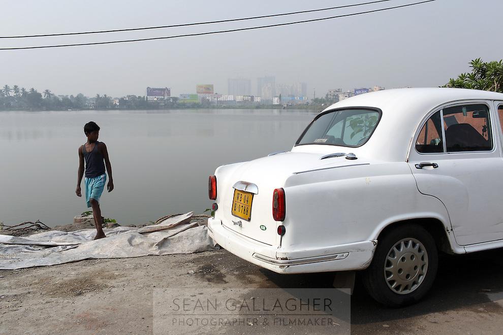 A young Indian boy stands near a car in Kolkata, India. November, 2013