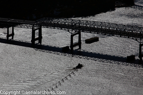 aerial photograph of a tug boat approaching the Tacony Palmyra Bridge which crosses the Delaware River between Pennyslvania and New Jersey northeast of Philadelphia