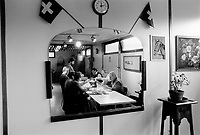 """Switzerland. Geneva. Garbage collectors. Lunch time. Workers sit at a table and eat the """"fondue"""" (melted cheese), which is a swiss food speciality. Painting of a horse and flowers, two swiss flags, a watch and a large mirror are on the wall.  © 1991 Didier Ruef"""