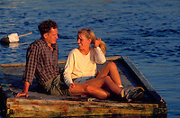 Young couple sitting on a dock.