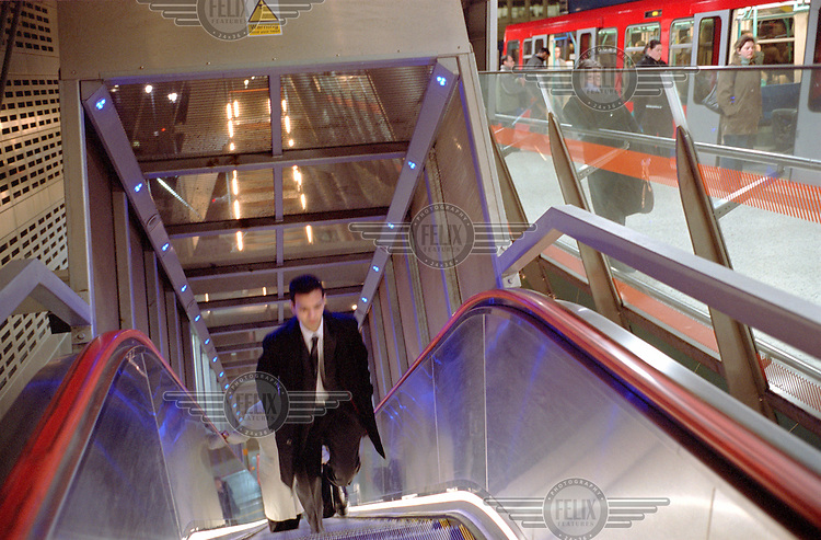 A commuter travels up an escalator on his way to a London Underground DLR (Docklands Light Railway) tube train.