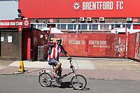 A Brentford fan waves goodbye to the stadium as he cycles past the ground ahead of their last ever game at Griffin Park during Brentford vs Swansea City, Sky Bet EFL Championship Play-Off Semi-Final 2nd Leg Football at Griffin Park on 29th July 2020