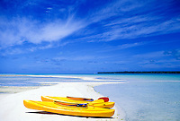 Two kayaks on white sand near a blue lagoon off Aitutaki, Cook Islands