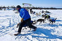 Checker Tyrell Seavey leads Hans Gatt to a parking spot at the Cripple checkpoint 1/2 way into the race during the 2010 Iditarod