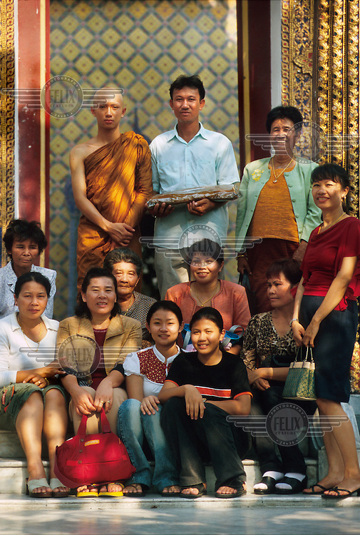 A young boy surrounded by his family on his first day as a monk. His family will leave him behind in the temple.