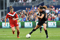 USWNT midfielder Lauren Cheney (12) controlling the ball in front of Christina Julien, forward Canada.