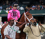 """April 18, 2014 Groom leading Sisterly Love holds up a """"We're Number One"""" finger after she wins the G3 Doubledogdare Stakes at Keeneland, with jockey Stewart Elliott"""