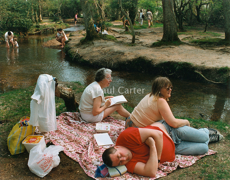 Family picnic next to a river in the New Forest.