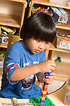 Preschool ages 3-5 boy building tower from colored connecting plastic cubes vertical