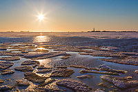 Midnight sun in the northern sky over the melting ice on Colleen Lake, oil drilling rigs of the Prudhoe bay oil fields in the distant horizon, Alaska.