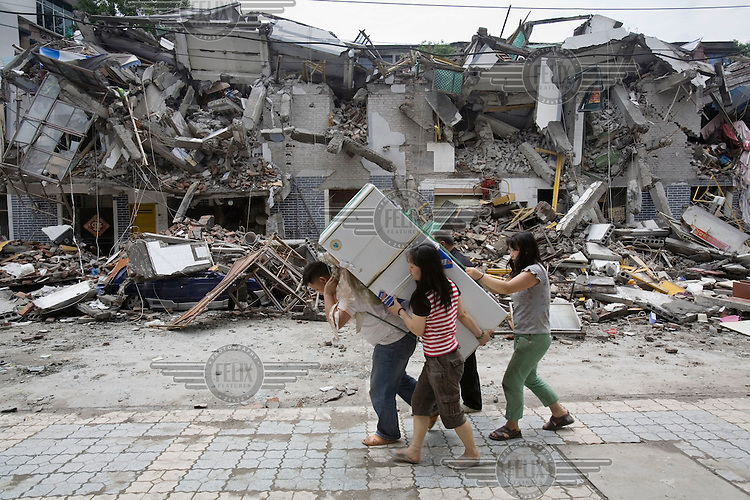 A family salvages a fridge and the last few remaining belongings that survived the recent Sichuan earthquake of 12/05/2008, which measured 8.0 on the Richter scale.