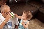 13 month old baby girl at home with father who is her primary caregiver talking about and playing with nesting stacking boxes horizontal