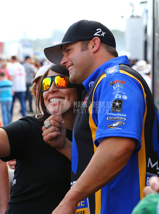 Mar 14, 2015; Gainesville, FL, USA; NHRA funny car driver Matt Hagan poses for a selfie with a fan during qualifying for the Gatornationals at Auto Plus Raceway at Gainesville. Mandatory Credit: Mark J. Rebilas-