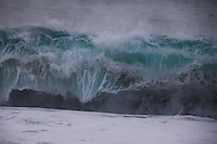 Thick shorebreak wave and foam at sunset on the North Shore of O'ahu.