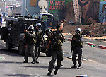An Israeli soldier hurls tear gas canister at Palestinian youths during the clashes at the Qalandia checkpoint between the West Bank city of Ramallah and Jerusalem on March 17, 2010. Israel on Wednesday lifted its tight restrictions on Palestinian access to Jerusalem's holiest shrine and called off an extended West Bank closure after days of clashes between Palestinians and Israeli security forces. While there were no reports of new clashes in Jerusalem, sporadic violence broke out Wednesday in the West Bank. Photo by Issam Rimawi