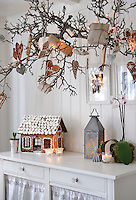 A branch taken from the pear tree in the garden has been used to display festive Christmas decorations in the dining area