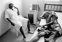 """Cameroon. Douala. """"L'Aquintinie"""" hospital. Day service.                                                                                                   Aids infection. Young woman HIV Aids positive with her sister. The woman lying down in bed receives some drugs because of bad side effects of her anti-retroviral  (ARD) treatment. © 2001 Didier Ruef"""