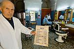 Piero (77 years old) working and posin in their shop in via Arborea, Sassari