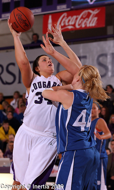 SIOUX FALLS, SD - DECEMBER 9:  jamey Hofer #34 of the University of Sioux Falls looks for the hook shot against Ashley Mailey #44 of Dakota Wesleyan in the second half of their game Wednesday night at the Stewart Center in Sioux Falls. (Photo by Dave Eggen/Inertia)