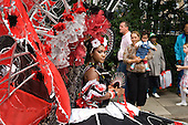 Spectators watch a Carnival Queen lead her band on Children's Day at Notting Hill Carnival