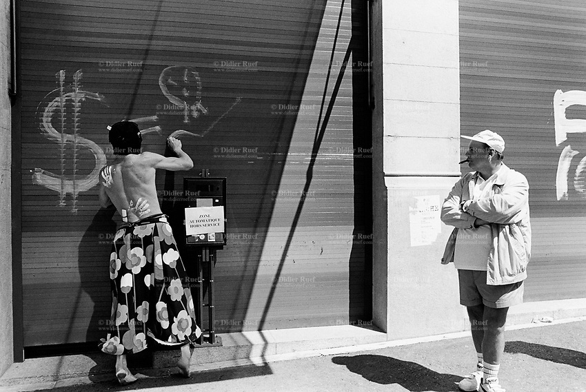 Switzerland. Geneva. Protest against the World Trade Organization (WTO) agreement . An old man, wearing a pair of shorts and a cap, smokes a cigar while a young man, a demonstrator dressed with a flowers pareo, stripped to the waist, barefeet and a black mask on the face, writes a graffiti on the metal curtain of a bank. Handprint on his back. The pāreu or pareo was used only to refer to women's skirts, as men wore a loincloth, called a maro. Nowadays the term is applied to any piece of cloth worn wrapped around the body, worn by males or females. © 1998 Didier Ruef