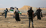 Palestinian women carry tires during clashes with Israeli security forces in tents protest where Palestinians demanding the right to return to their homeland, at the Israel-Gaza border, in Khan Younis in the southern Gaza Strip, on May 11, 2018. Photo by Ashraf Amra