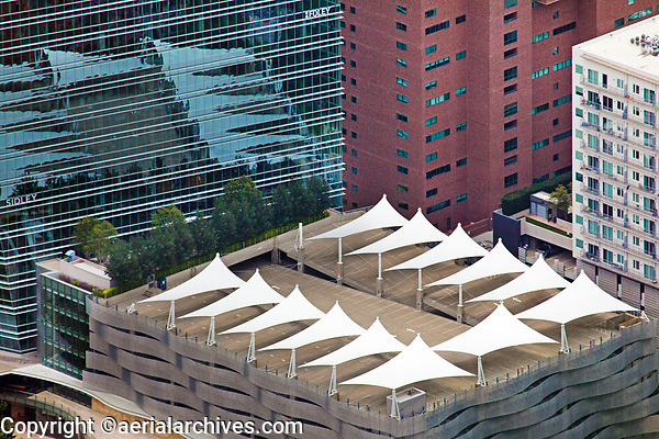 aerial photograph of shade structures at the top of the parking structure and a roof garden at Cedar Springs Road, Dallas, Texas, the shade structures are reflected in the glass of 2021 McKinney Avenue high rise