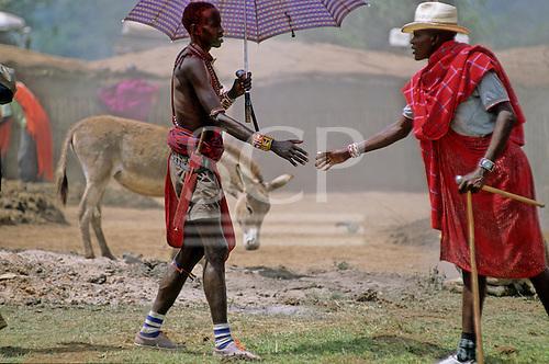 Lolgorian, Kenya. Siria Maasai greeting a fellow tribesman with an umbrella at the manyatta set up for the eunoto ceremony.