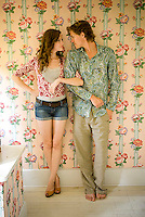 Young couple standing against floral wallpaper