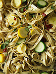 Close up image of fettuccine with zucchini and crookneck squash sliced into rounds, and fresh oregano