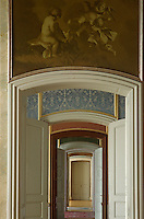 A grisaille scene above a doorway down an enfilade of open double doors