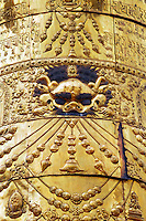 Kirtimukha, or Face of Glory, doorway guardian with net of jewels hanging from mouth. Detail from dhvaja, or Victory Banner, representing Buddha's victory over the evil influences, or maras, atop Drepung Monastery, Lhasa, Tibet, China.