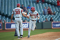 Cole Austin (16) of the Arkansas Razorbacks slaps hands with third base coach Nate Thompson (30) during the game against the Oklahoma Sooners in game two of the 2020 Shriners Hospitals for Children College Classic at Minute Maid Park on February 28, 2020 in Houston, Texas. The Sooners defeated the Razorbacks 6-3. (Brian Westerholt/Four Seam Images)
