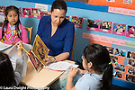 Afterschool homework help program for Headstart graduates Grades K-3 female teacher working with students in grades K & 1 holding out books in Spanish to student