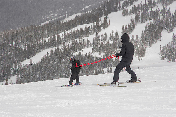 Father teaching son to ski at Loveland Ski Area, Colorado, .  John leads private ski trips to Front Range and Summit County Ski Areas in Colorado.