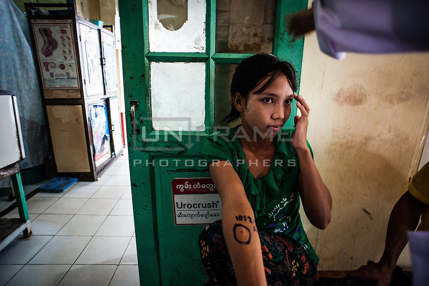 Patient of local clinic in Bago waits for the results of the allergy tests with time of the test marked on her hand