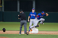 AZL Rangers shortstop Yonny Hernandez (59) leaps over AZL Giants first baseman Nathanael Javier (47) after applying the tag on September 4, 2017 at Scottsdale Stadium in Scottsdale, Arizona. AZL Giants defeated the AZL Rangers 6-5 to advance to the Arizona League Championship Series. (Zachary Lucy/Four Seam Images)