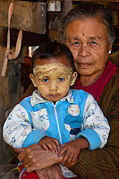 Myanmar, Burma.  A Grandmother and her Grandson, Inle Lake, Shan State.  The little boy has thanaka paste on his face, a Burmese cosmetic sunscreen.