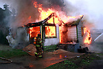 Fireman from East Jefferson Fire and Rescue approaches a fully engulfed house fire.